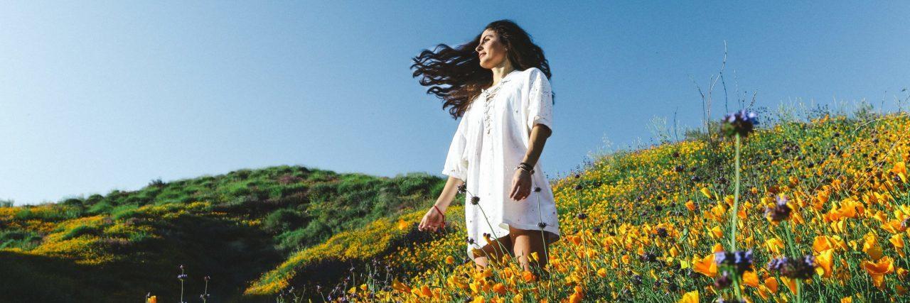 woman in flower field looking hopeful