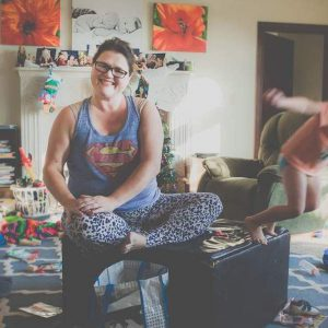 Mother sitting in middle of messy living room, smiling at camera while a child jumps off a couch and one makes a mess on floor