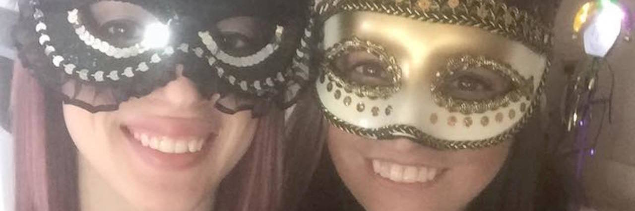 two women wearing gold and silver masks