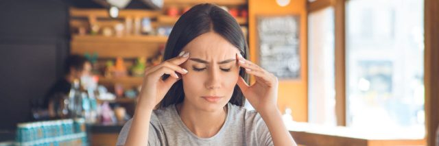woman getting a migraine at a restaurant