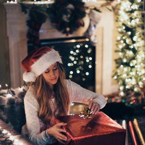 woman alone at christmas opening large present
