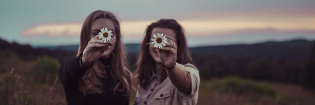 two women holding daisies for camera and smiling at sunset