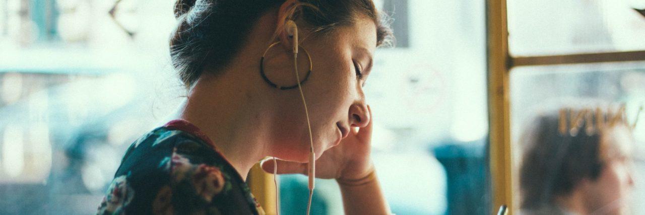 woman with earphones alone in public