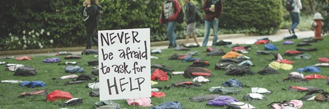 """backpacks on ground of college campus for the """"Send Silence Packing"""" project"""