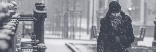 woman walking along street in snowstorm