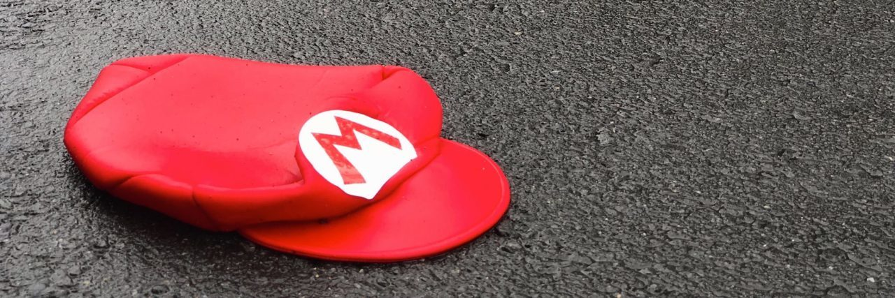 super mario hat lying on pavement in road abandoned