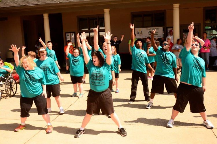Group of people with Down syndrome wearing a green shirt and dancing in unison with arms up high