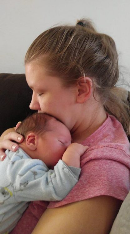 mother in a pink shirt with her hair up in a ponytail and not wearing makeup holding her newborn baby against her chest
