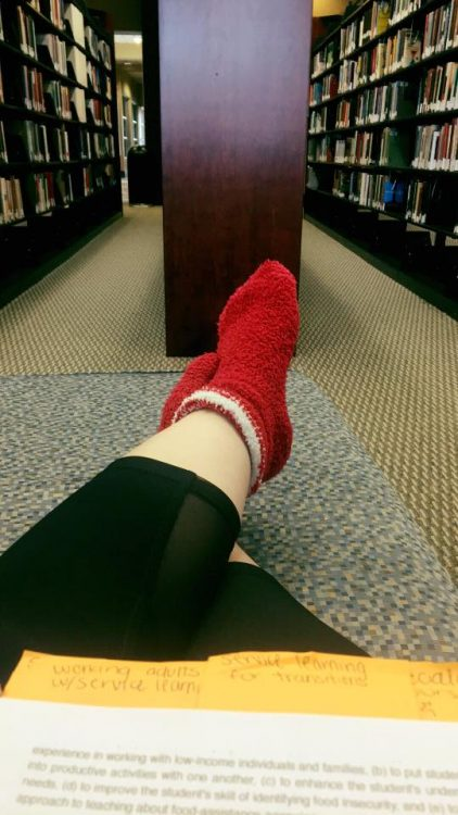 woman wearing red fuzzy socks in the library