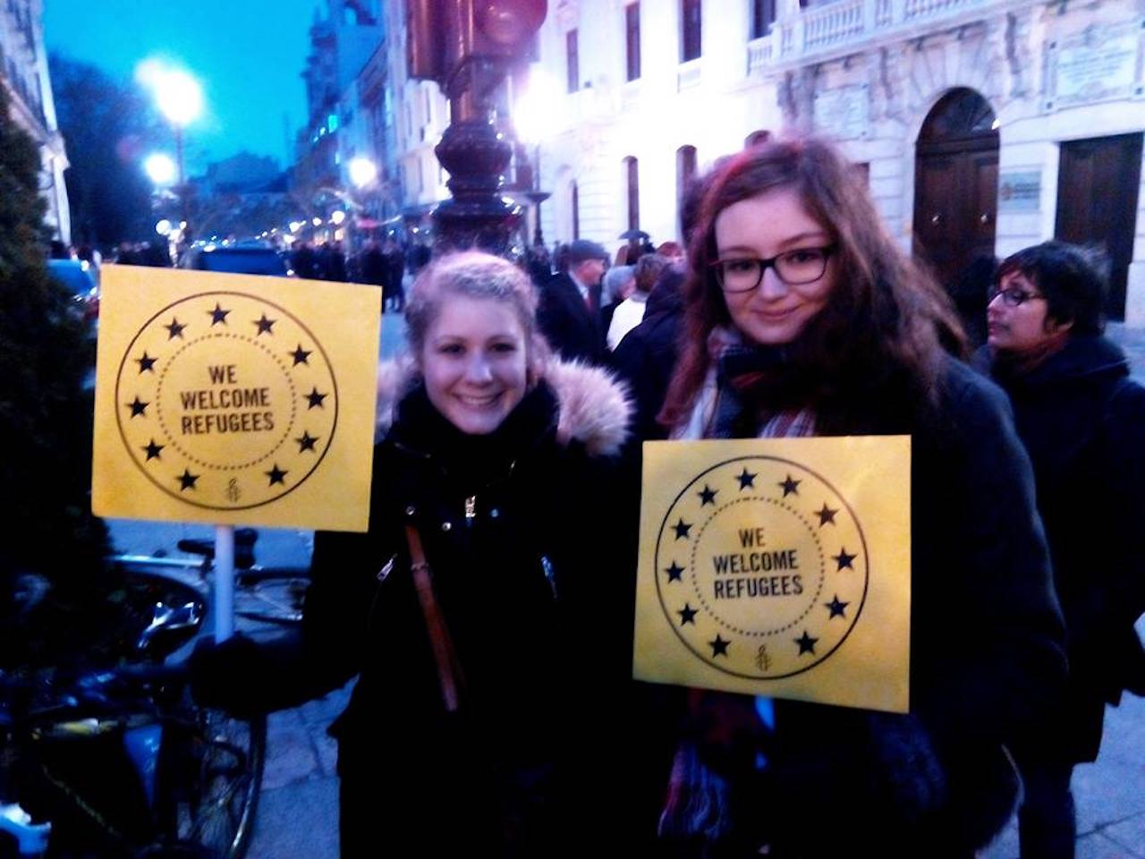 two young women at a march holding signs that say 'we welcome refugees'
