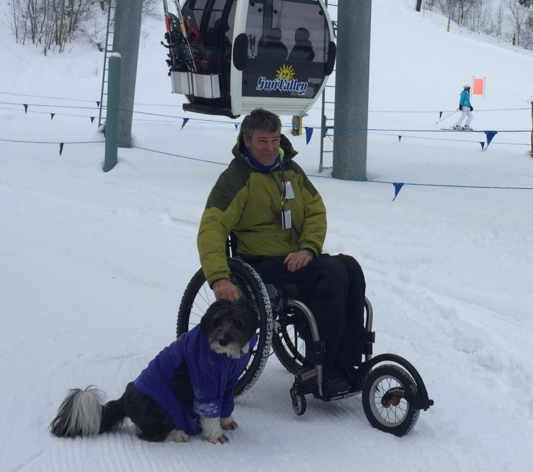 man in wheelchair in snow with freewheel wheelchair attachment on front of wheelchair