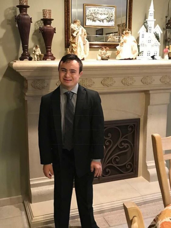 Young man with Down syndrome wearing a suit and posing by a white marble fireplace.