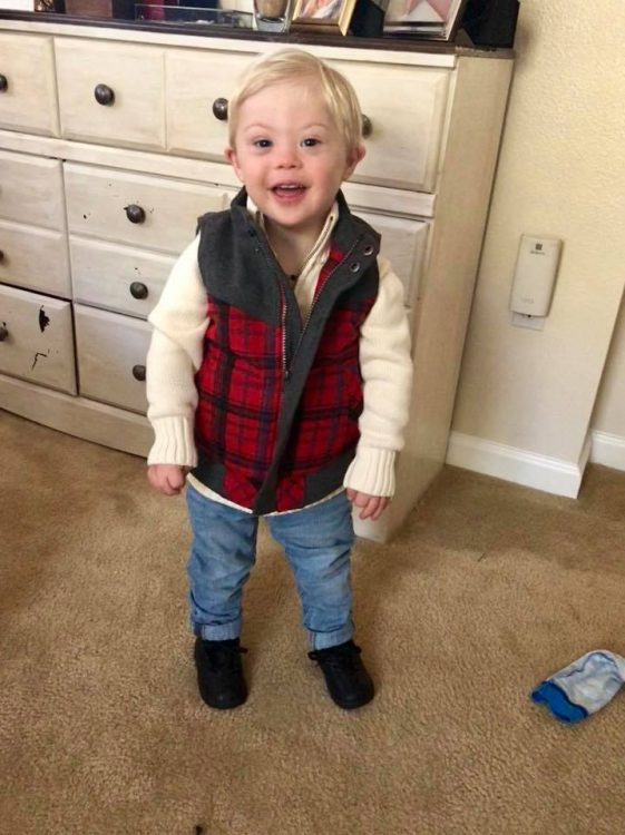 Little boy with Down syndrome posing for the camera, full body shot and he is wearing a white sweater with a red checkered vest and jeans.