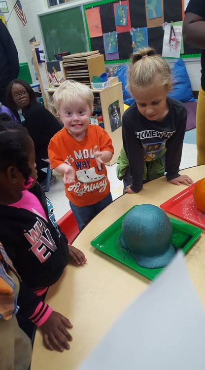 Little boy with Down syndrome at school. He is wearing an orange shirt and looking at the camera with an excited look on his face, big grin and clenching fists.
