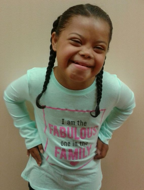 Little girl with Down syndrome posing at camera hands on her hips. She has two braids and a mint colored long sleeved shirt.