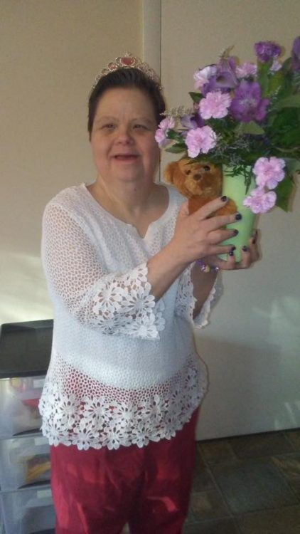 Woman with Down syndrome wearing a tiara, holding a vase of flowers and a teddy bear.