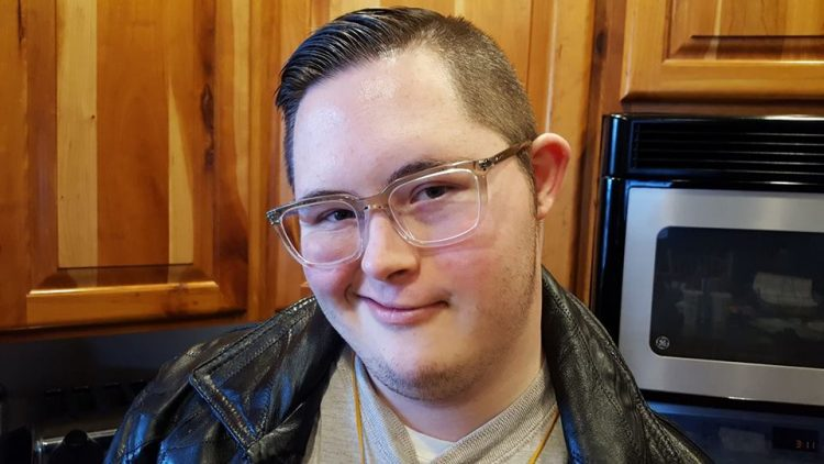 Young adult with Down syndrome smiling at camera. Close up of face, he wears glasses and a leather jacket.