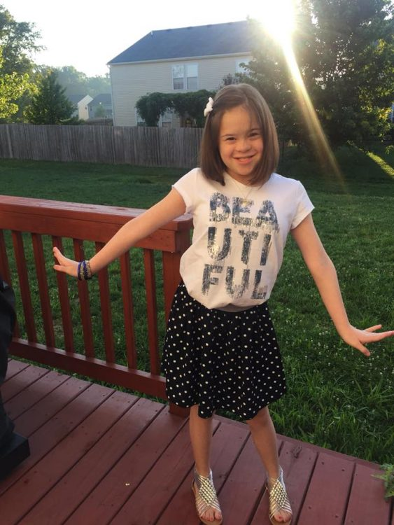 """Pre teen with Down syndrome posing for a photo. She wears a pale pink shirt that says, """"Beautiful"""" and a black skirt. She is standing on a red-stained porch."""