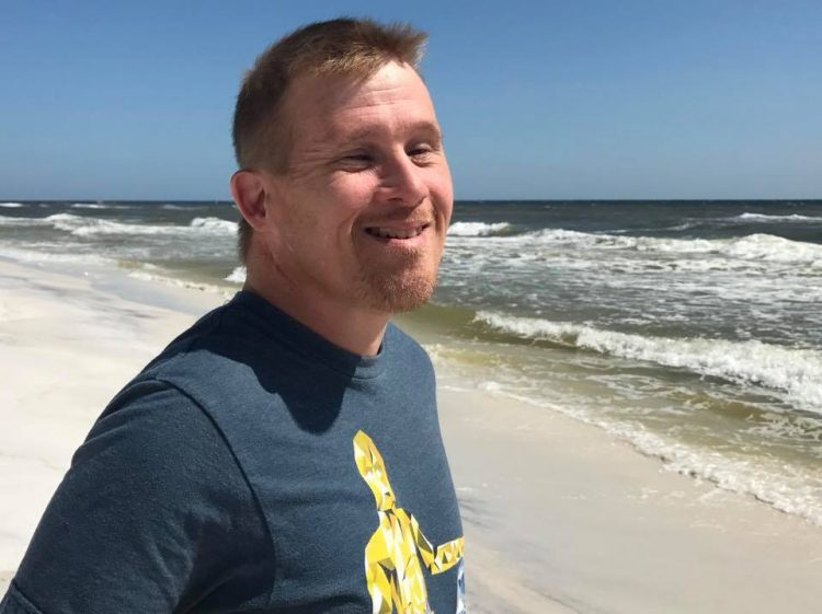 Man with Down syndrome looking at the camera and smiling. He has a goatee and is posing at the beach.
