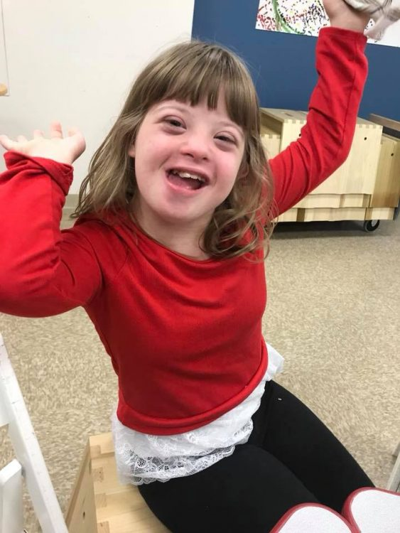 Little girl with Down syndrome wearing a red sweater and pumping her arms up.