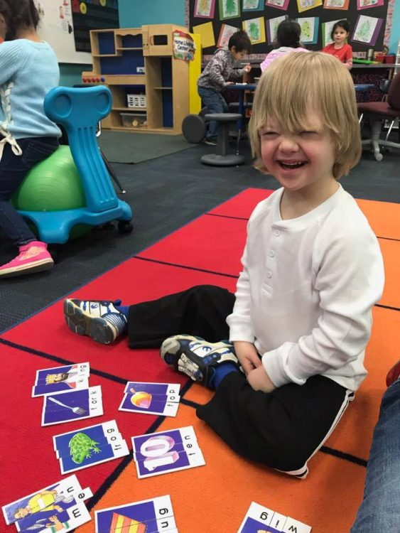 Little boy with Down syndrome at school, sitting on a rug, flashcards on the floor and he smiles at camera.