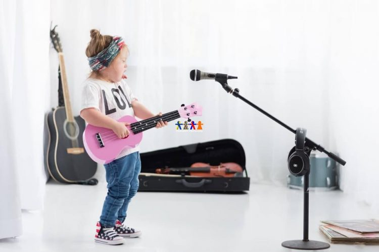 Little girl with Down syndrome in studio photo. She is holding a pink guitar, a microphone in front of her. Violin case in the background with violin inside and a guitar sitting in the corner.