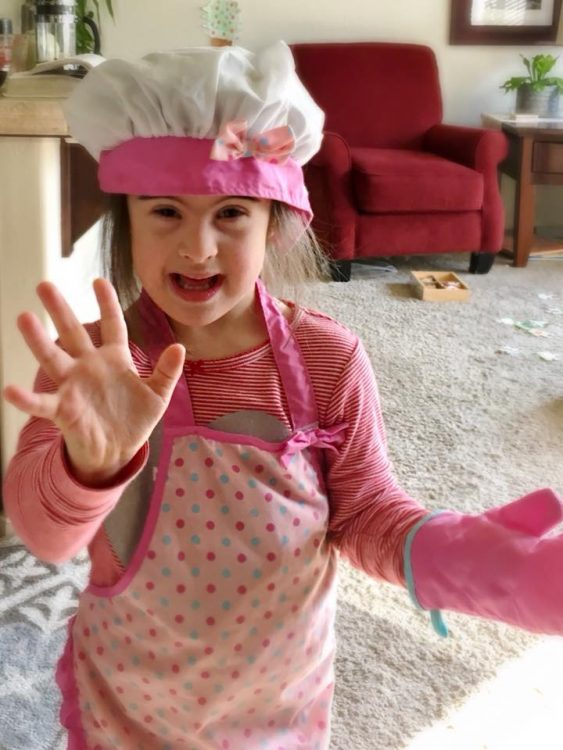 Little girl with Down syndrome wearing a pink chef's costume, including hat, apron and over mitt. She is waving at the camera with her other hand.