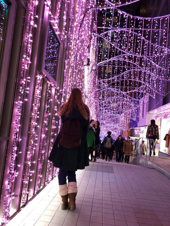 woman walking outside among christmas lights with her legs bending to the left