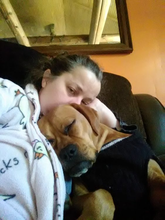woman lying with dog on couch, dog's head on her chest