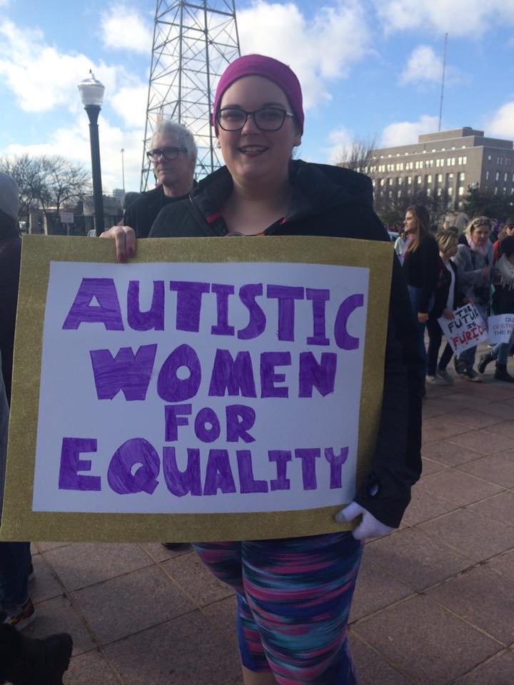 a woman with a sign that says autistic women for equality