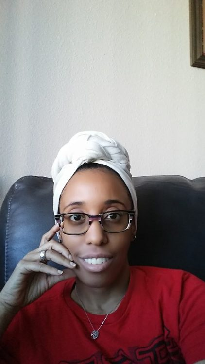 woman wearing glasses and a white head scarf sitting on a couch