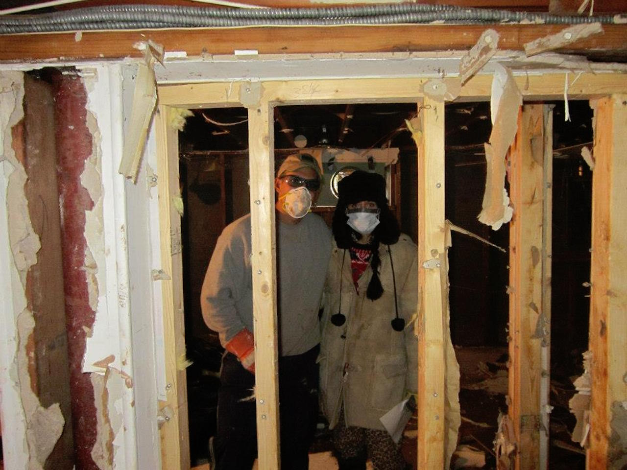 man and woman wearing face masks and standing in their flooded basement