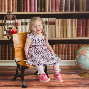Little girl with down syndrome sitting on small wooden bench with a bookshelf as background.