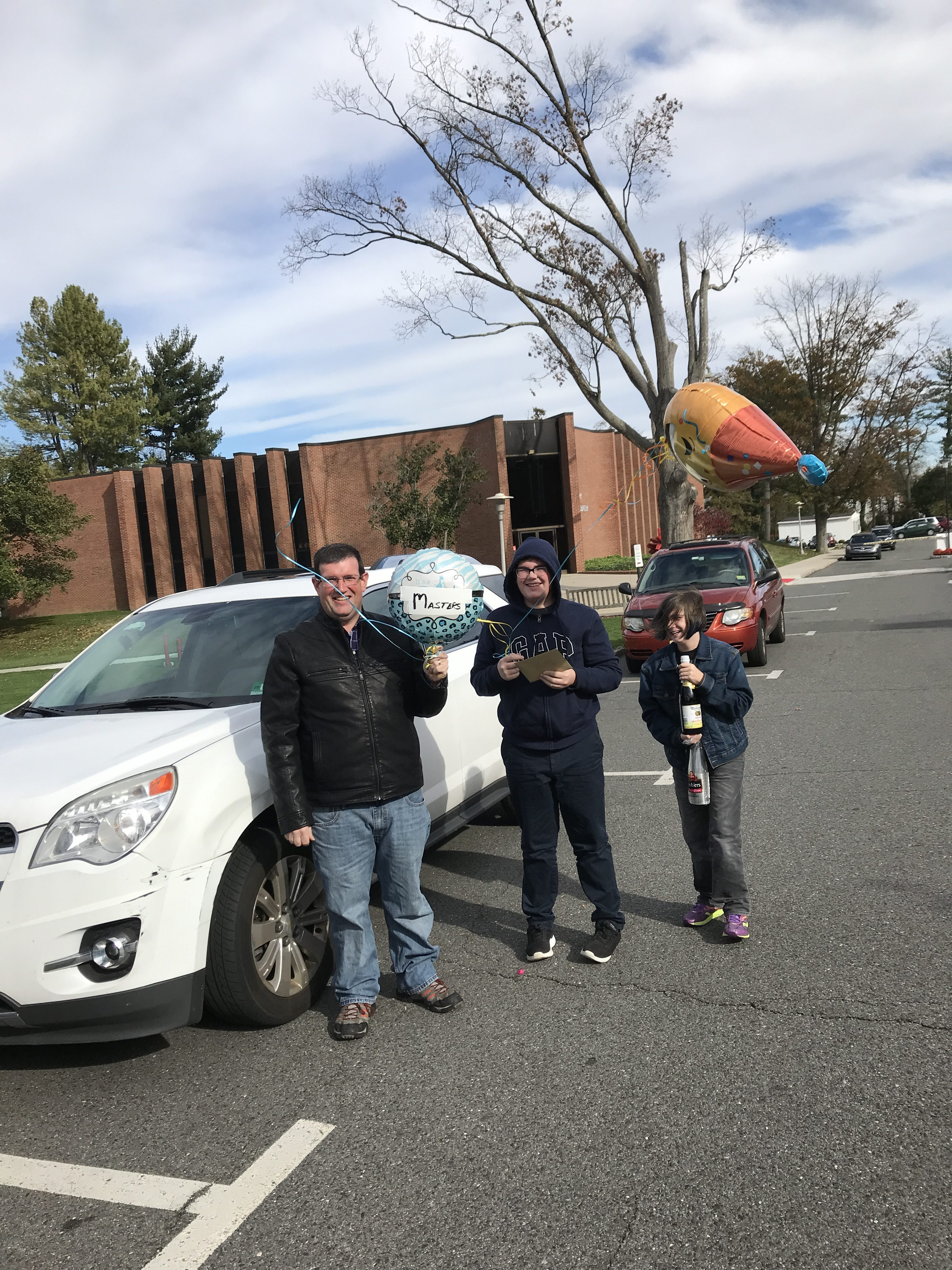 author's husband and two children waiting outside for her with balloons