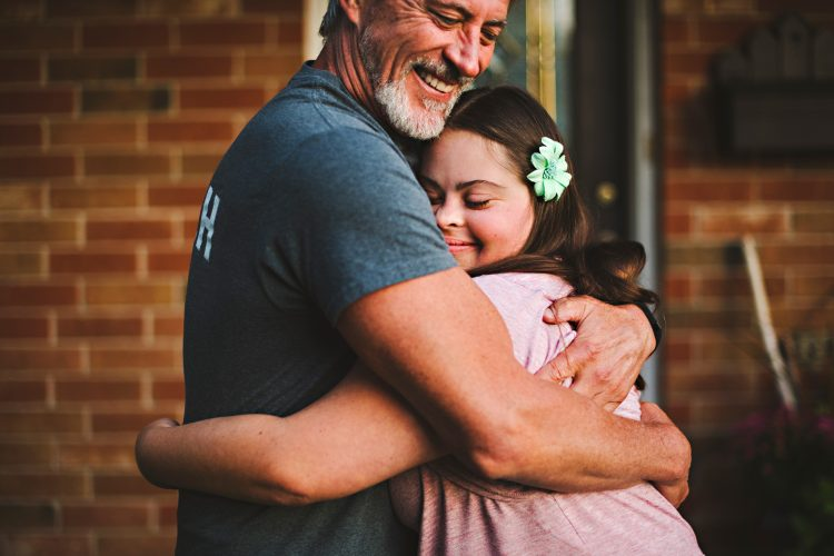 father hugging daughter with Down syndrome, daughter is closing her eyes, enjoying the hug, dad is happy and smiling. Daughter seems to be a teenager or young adult.