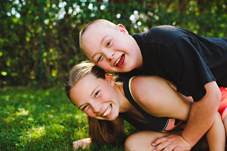 Brother and sister. They both smile at camera, brother with down syndrome is on top of sister.