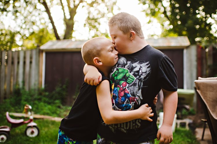 Two brothers hugging. Older brother has Down syndrome and kissing younger brother on forehead. Little brother is closing his eyes, letting the love in, and hugging his brother tight.