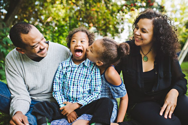 Family of four, mom and dad at the ends, sister kissing brother with Down syndrome who is smiling big and happy