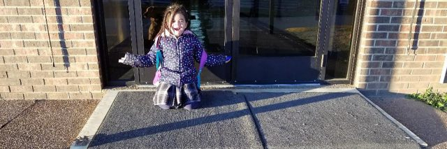 Lylly's daughter smiles while kneeling at the ramp her principal built for her mother's wheelchair.