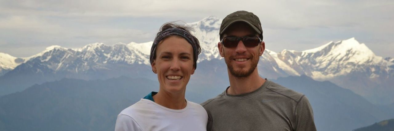 Annie and Brad smiling in front of a mountain range in Colorado