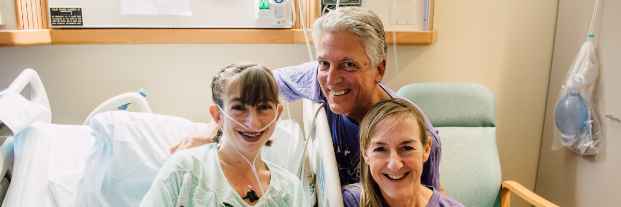 Girl sitting in hospital bed with oxygen and monitors, she is smiling, posing with her dad and mom.