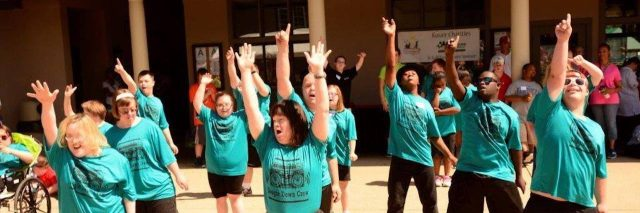 People with Down syndrome wearing green shirts and dancing in unison, arms up high, powerful