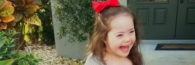 Little girl with Down syndrome standing outdoors smiling