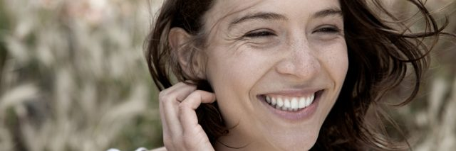 woman laughing and tucking her hair behind her ear