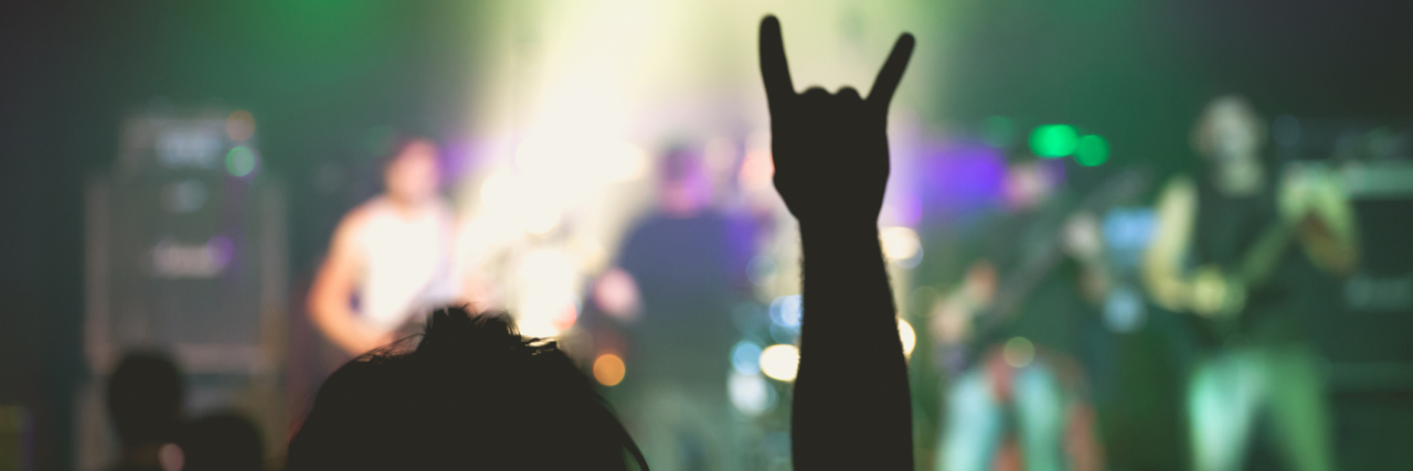 small rock music concert with focus on fan raising horns symbol into air