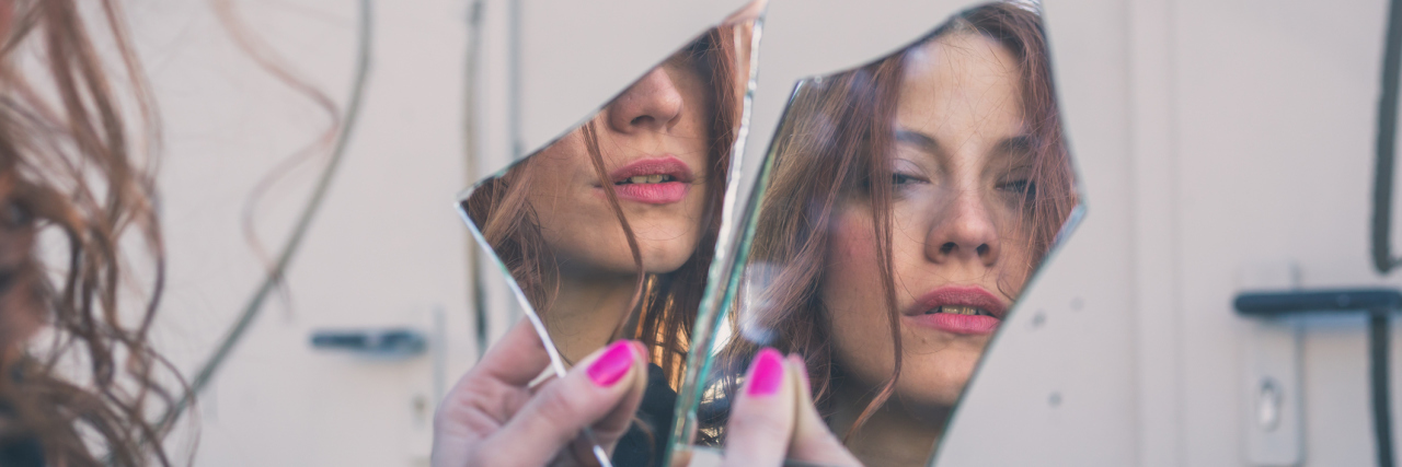 Woman looking at herself in a broken mirror