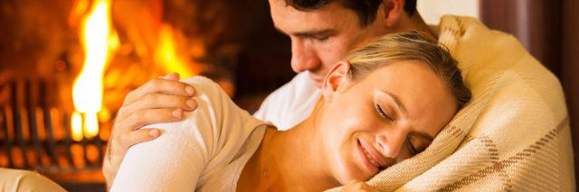 woman cuddling with her husband on the couch in front of the fireplace