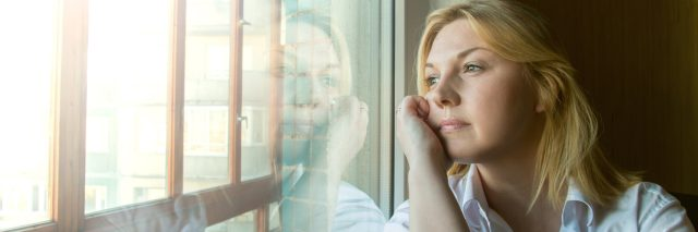 Woman looking out window lost in thought rumination