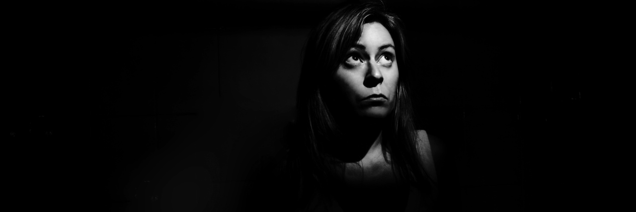 A woman in the shadows, looking afraid.
