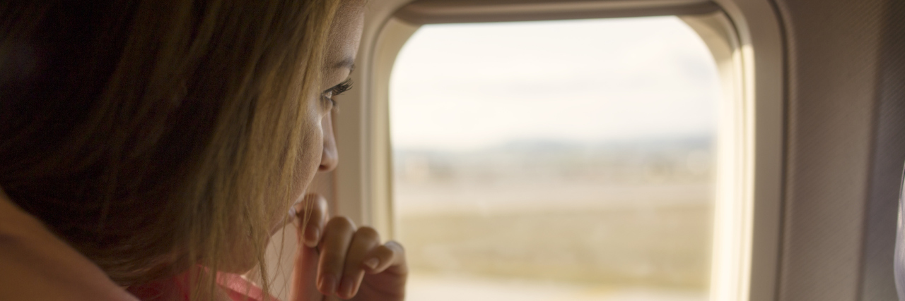 woman looking out of plane window nervous scared